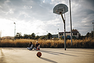 Two young men sitting on outdoor basketball court - JRFF000487