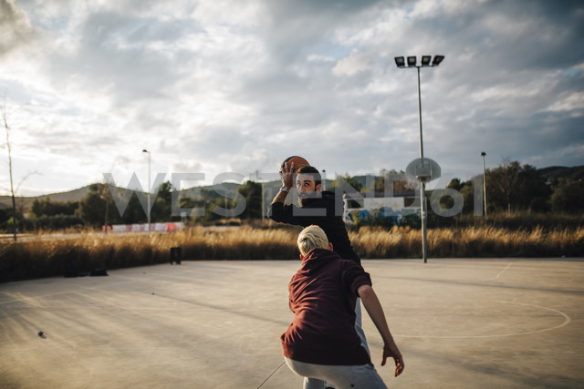 Two young men playing basketball on an outdoor court - JRFF000490