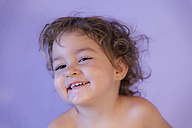 Portrait of smiling little girl in front of purple background - ERLF000145