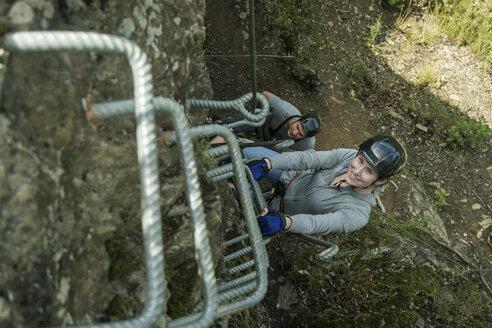 Germany, Westerwald, Hoelderstein, man and woman climbing on via ferrata - PAF001552