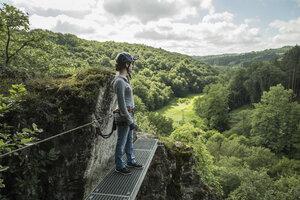 Germany, Westerwald, Hoelderstein, woman on via ferrata looking at view - PAF001555