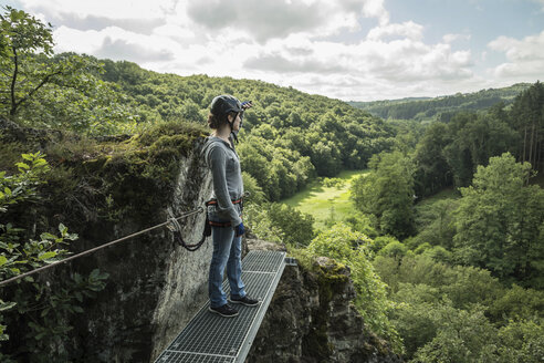 Germany, Westerwald, Hoelderstein, woman on via ferrata looking at view - PAF001555