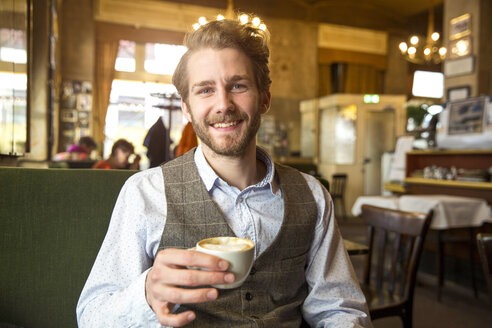 Portrait of smiling young man in a cafe - SUF000061