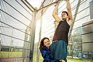 Young woman helping boyfriend doing chin-ups - SUF000070