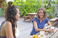 Two happy woman sitting at table talking - KNTF000239