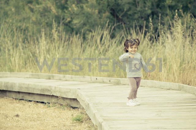 Spain, laughing little girl standing on wooden boardwalk - ERLF000148
