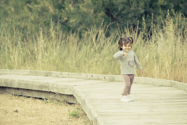 Spain, laughing little girl standing on wooden boardwalk - ERLF000148
