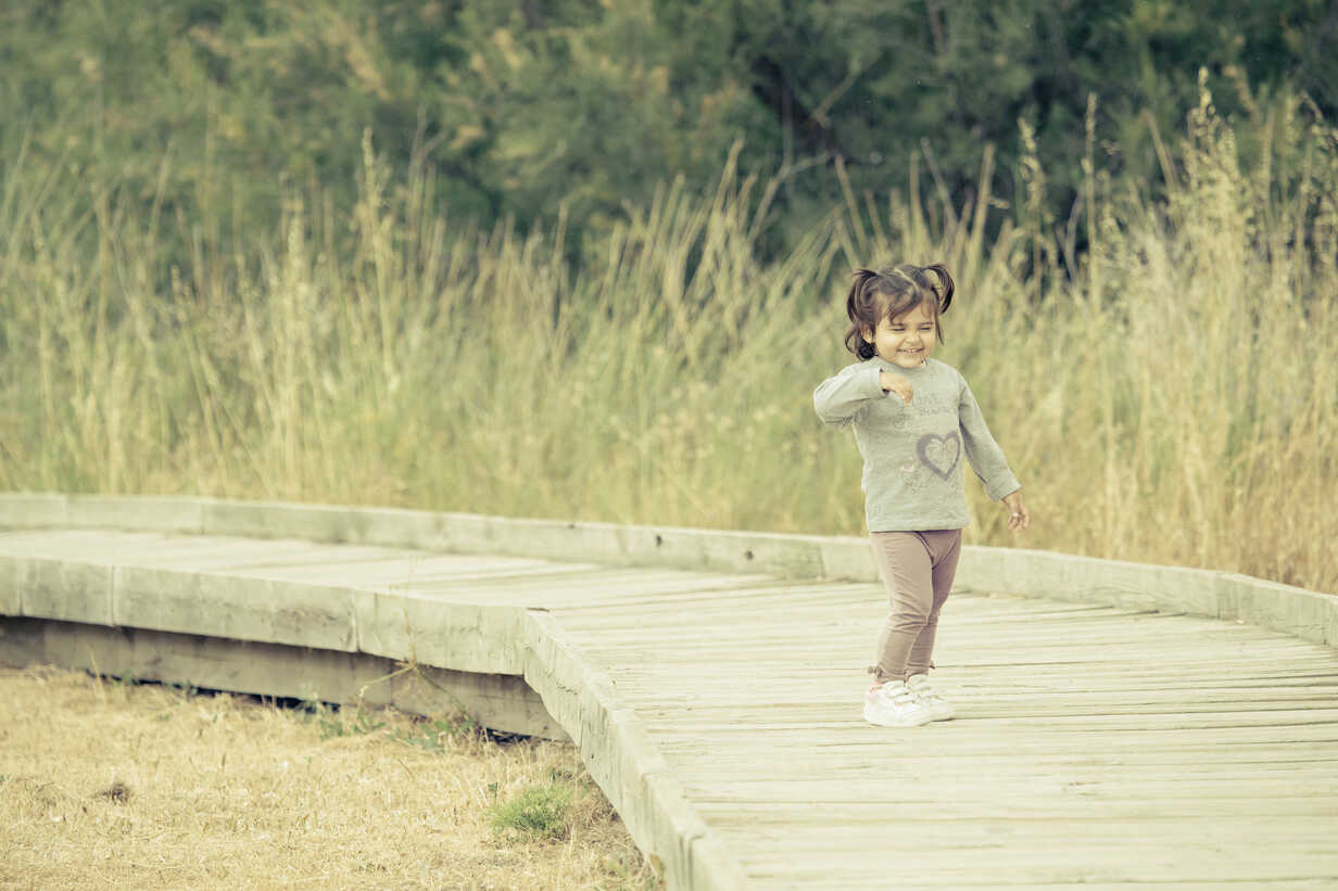 Spain, laughing little girl standing on wooden boardwalk - ERLF000148 - Enrique Ramos/Westend61
