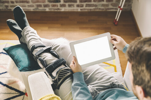 Injured man with knee brace using a tablet computer at home - MFF002726