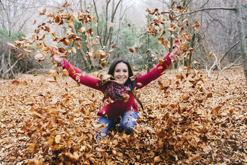 Woman throwing autumn leaves in the air - GEMF000767
