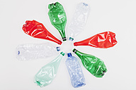 Circle of different empty flexed plastic bottles on white ground - GWF004642