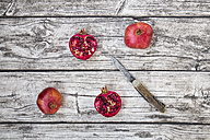 Two whole and two halves of organic pomegranate and a pocket knife on wood - LVF004587