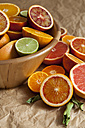 Wooden bowl of citrus fruits on crumpled brown paper - VABF000259
