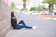 Spain, Tenerife, smiling teenage girl  with headphones and smartphone sitting on the ground - SIPF000217