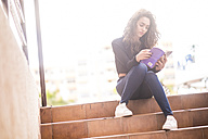 Teenage girl sitting on steps reading a book - SIPF000220