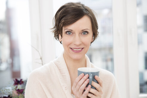 Portrait of smiling woman holding cup - FMKF002423
