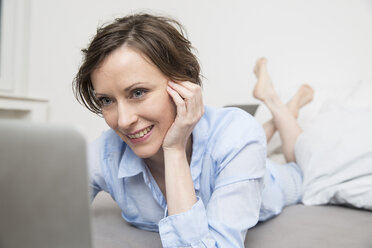 Happy woman lying on bed using laptop - FMKF002432