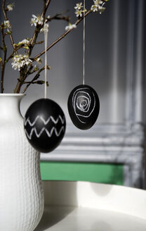 Two Easter eggs painted with blackboard paint and chalk hanging on blossoming twig - GISF000200
