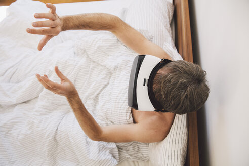 Man in bed wearing virtual reality glasses moving his hands - MFF002735