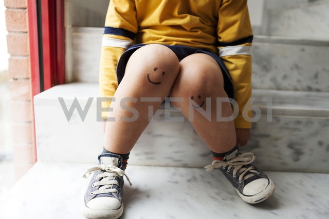 Boy sitting on stairs with smiley faces on his knees - VABF000272