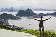 Brazil, Rio de Janeiro, tourist standing at view point, raising arms - MAUF000252