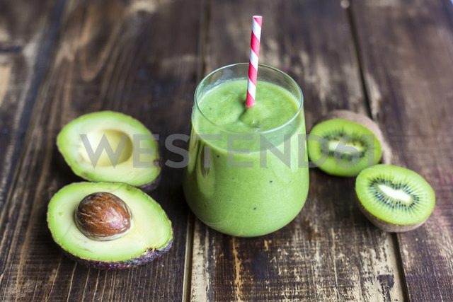 Glass of avocado kiwi smoothie and sliced fruits on wood - SARF002608