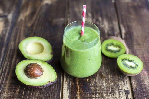 Glass of avocado kiwi smoothie and sliced fruits on wood - SARF002608