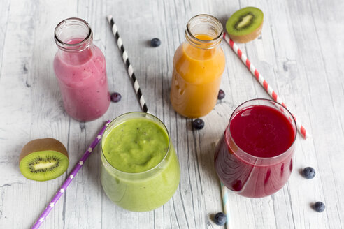 Glasses of four different smoothies and fruits on wood - SARF002611
