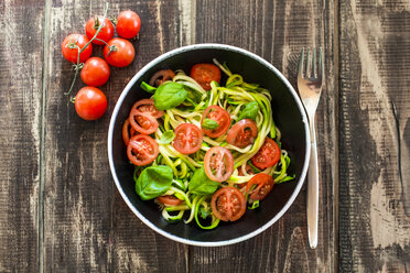 Zoodles, zucchini spaghetti, with tomato and basil in bowl - SARF002614