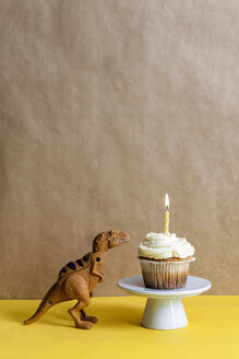 Toy dinosaur and cup cake with lighted candle on a cake stand - VABF000284