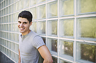 Portrait of smiling young man standing in front of wall - RAEF000920