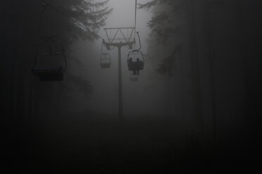 Germany, silhouettes of people using chairlift at haze - CRF002743