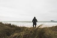 France, Bretagne, Finistere, Crozon peninsula, man standing at the coast - UUF006651