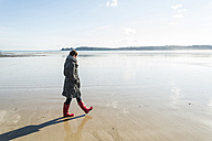 France, Bretagne, Finistere, Crozon peninsula, woman walking on the beach - UUF006657