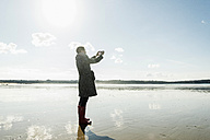 France, Bretagne, Finistere, Crozon peninsula, woman taking a picture on the beach - UUF006660