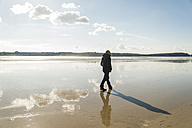 France, Bretagne, Finistere, Crozon peninsula, man walking on the beach - UUF006663