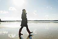 France, Bretagne, Finistere, Crozon peninsula, woman walking on the beach - UUF006666