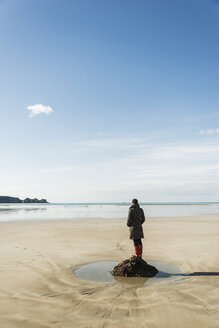 France, Bretagne, Finistere, Crozon peninsula, woman standing on the beach - UUF006669