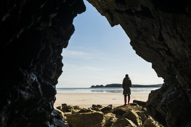 France, Bretagne, Finistere, Crozon peninsula, woman standing on the beach as seen from rock cave - UUF006672