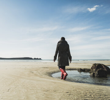France, Bretagne, Finistere, Crozon peninsula, woman walking on the beach - UUF006678