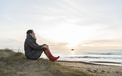 France, Bretagne, Finistere, Crozon peninsula, woman sitting at the coast - UUF006684