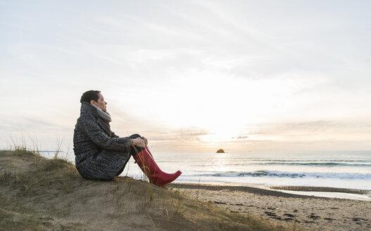 France, Bretagne, Finistere, Crozon peninsula, woman sitting at the coast - UUF006684