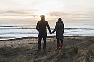 France, Bretagne, Finistere, Crozon peninsula, couple standing at the coast at sunset - UUF006687
