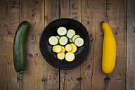 Yellow and green zucchini and bowl of zucchini slices on wood - LVF004610