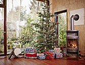Christmas presents under Christmas tree next to cozy fireplace - RHF001294