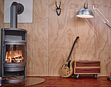 Electric guitar leaning on chest of drawers near fireplace - RHF001300