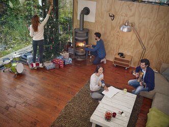 Friends preparing for Christmas Eve in cozy living room - RHF001303