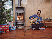 Man sitting on floor and playing electric guitar by Christmas tree - RHF001306