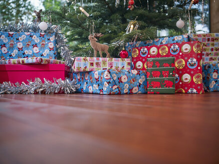 Christmas presents wrapped in colorful wrapping paper under Christmas tree - RHF001309