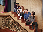 Friends sitting on wooden stairs having fun - RHF001312